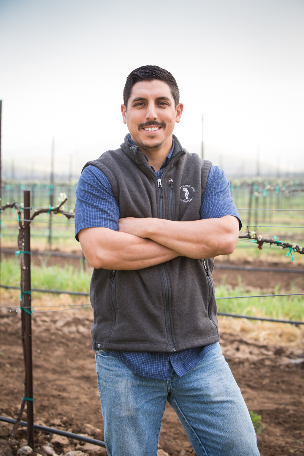 Greg Gonzales posing in front of a vineyard